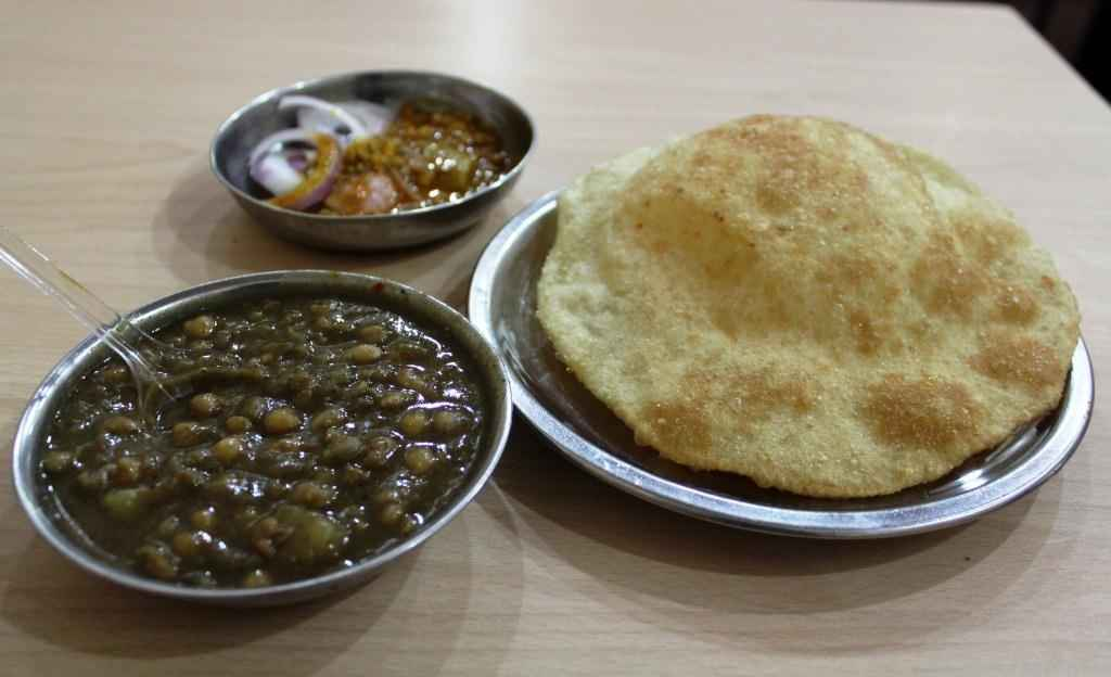 Bille di hatti  Chole bhature are common almost everywhere but bille di hatti gets you the most healthy bhaturas or it won't be wrong if you call them pooris, as they are made by a combination of maida, aata and sooji (wheat flour, flour and semolina). Also their chole are gravy rich which are heavenly spiced and retain a corner in your memory. Not to forget the amazing lassi offered by this spot makes chole bhature and lassi a unavoidable combination at this place.  Where: Kamla Nagar  Price: Rs.50 per plate  Timings: 7:00 AM to 4:00 PM  Nearest Metro Station: Vishwavidyalaya  Explore More: https://www.delhipedia.com