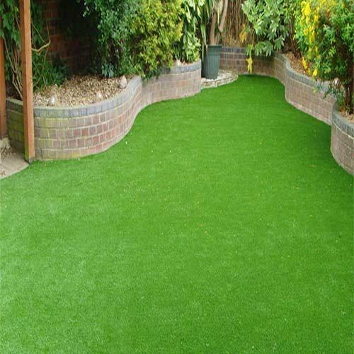 Artificial Grasses  We Sundek Sports Systems are manufacturers of Artificial Grasses in Mumbai. As well as in India. Sundek Sports Systems is having a leading position in offering Artificial Grasses to valuable customers. Artificial Grass/Artificial Turf manufacture uses the same machines as conventional carpet tufting, adapted to the longer lengths required in many products.Sundek Sports Systems has extensive experience in the manufacturing, construction, installation and development of artificial turf/ artificial grass for landscaping, leisure, playgrounds and mini sports installations. We have the knowledge and skills to advise you on each system. Our product range is suitable for almost any flooring application.   Sundek Sports System offers Artificial Grasses (Sun Turf). Sun Turf is the closest look -alike to natural grass, and has all the third party international speccifications and ratings with respect to Fire, Safety and Environment. The base surface will have to uniform and hard. It cannot be installed over an existing grass surface as that would make the Sun Turf (Artificial Grasses) dimensionally unstable and, due to the uneven nature of the base, the joints would also show. Hence the important requirement of a level base surface.  Features:      Helps to create a Green and Vibrant lawn all yar around.     Cost efective and affordable.     Commercial grade materials used.     Environmentally friendly.     UV stabilized, designed for outdoor use.     Enhance Property value.     Long lasting investment, 8-10 years lifespan.     Other Details:       Draincell, being an optional item, would be required if you preferred the surface water to quickly drain out from the surface, especially after a heavy monsoon shower. It has a 20mm thickness. Maintenance of the Sun Turf (Artificial Grasses) is absolutely minimal and very basic. It can be broomed/hoovered and even washed with a water hoseregularly, to keep it clean. The surface fibre will never come off in normal use.