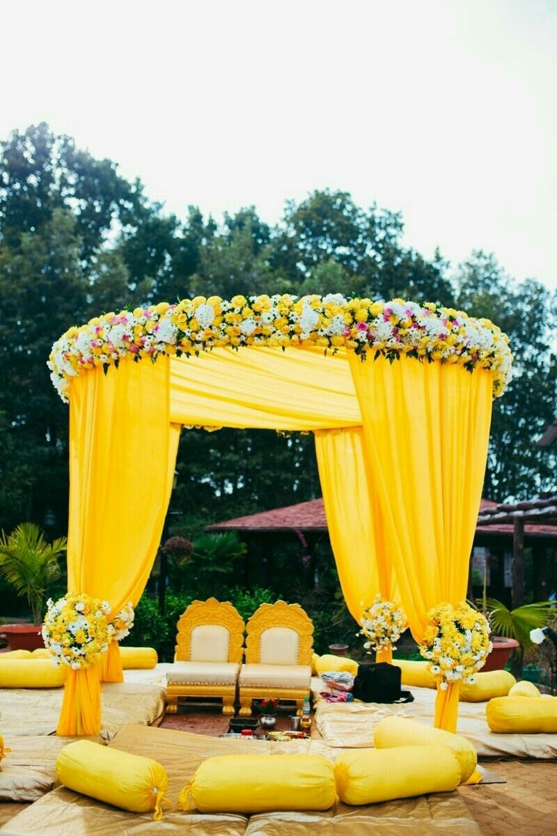 Give your day wedding a yellow theme! Shaadi mandap decorated with drapes, ample of comfortable seating space and floral bunches.
