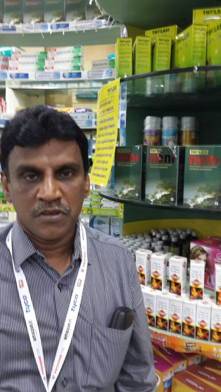 MD of thulasi pharmacy,  mr. Ramakrishnan in his store next to a new product noni a nutritional supplement - by Kumar Rajagopalan, Mumbai