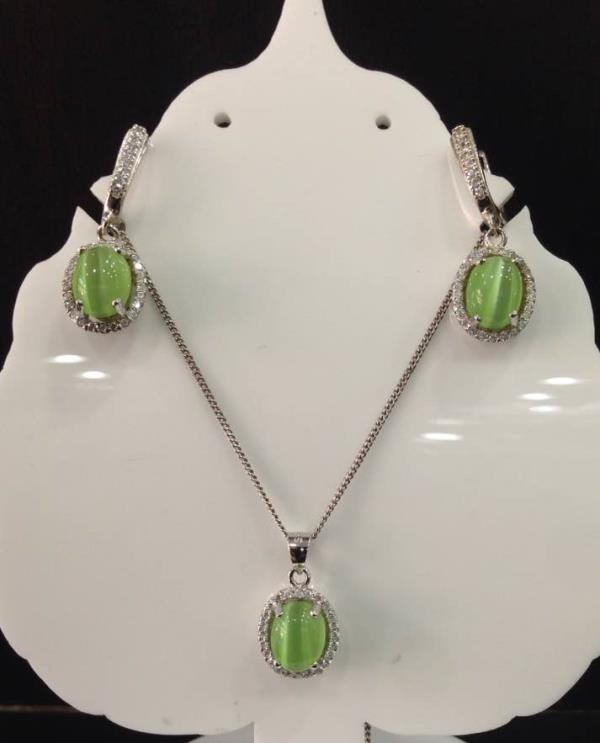 Green Cats Eye ( synthetic ) Pendant set with CZ stones. It's a simple design yet very attractive due to the glow of the cats eye stones. The earrings have an english locking and are quite light weight and comfortable. Also available in a darker green and subtle pink cats eye.