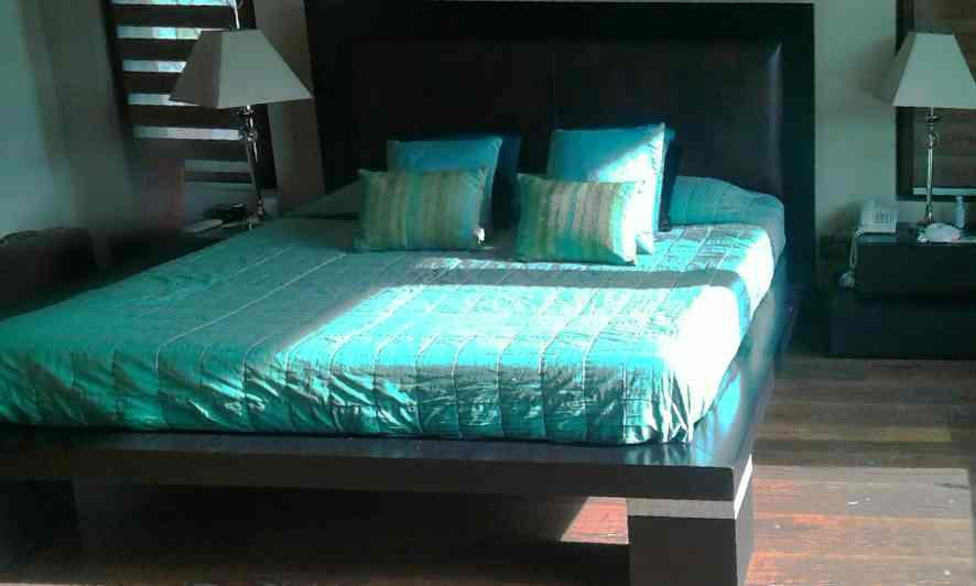 Wooden platform bed in matt finish.