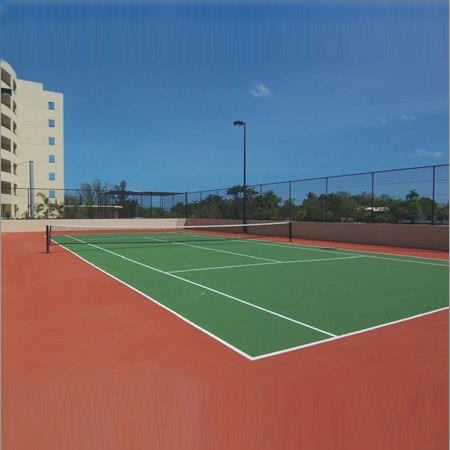 Outdoor Tennis Court Flooring  We Sundek Sports Systems are manufacturers of Outdoor Tennis Court Flooring in Mumbai.  As well as in India. Dimension:  Tennis is played on a rectangular, flat surface, usually grass, clay, or a hard court of concrete and/or asphalt. The court is 78 feet (23.77 m) long, and its width is 27 feet (8.23 m) for singles matches and 36 ft (10.97 m) for doubles matches. Additional clear space around the court is required in order for player to reach overrun balls. A net is stretched across the full width of the court, parallel with the baselines, dividing it into two equal ends. The net is 3 feet 6 inches (1.07 m) high at the posts and 3 feet (91.4 cm) high in the center.  Polywin Synthetic Flooring:  Preparation of strong and reliable base is a must for the construction of a synthetic hard court. The polywin synthetic material can be applied on asphalt or concrete base. The court can be prepared in different cushion thicknesses depending on level of players and budget. We also provide chain link fencing, lighting and storm water system in the court.