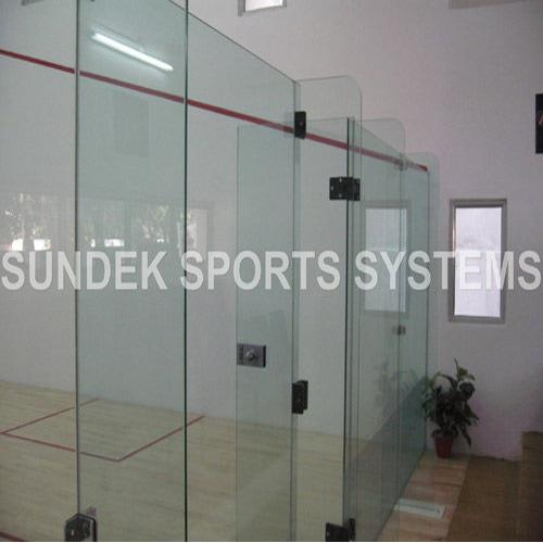 "Glass Back Wall for Squash Court  We Sundek Sports Systems are manufacturers of Glass Back Wall for Squash Court                                          in Mumbai.  As well as in India. Product Details: Color	Transparent Material	Glass  We supply and install Sundek ""Clear Tough"" free standing and maintenance free glass back wall system confirming the WSF (WORLD Squash Federation) requirement made of 12 mm micron clear toughened glass with 4 panels 1 door, 4 fins, fixtures & fittings and all other materials for erecting the glass wall system. The height of the glass wall is 2130 mm above the finish floor level. We will require 6400 mm clear opening between two sidewalls for installation of the glass back wall. We will also require a niche in each sidewall and a concrete sub floor outside of the court area. Details of these will be furnished on receipt of the order. Our skilled team trained under the official installers of international squash tournament will erect the glass wall completely with panels, fins, door lock etc and finished with suitable sealant."